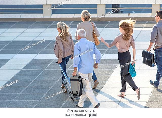 Five adults walking across paving slabs