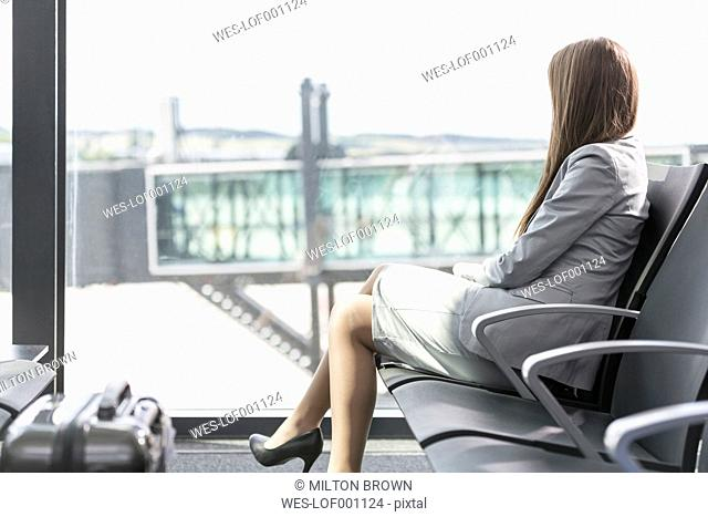 Businesswoman at the airport looking out of window