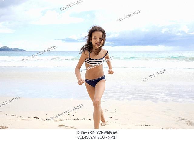 Girl running on beach in Seychelles