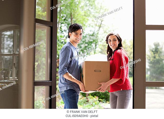 Young couple carrying cardboard box into new house