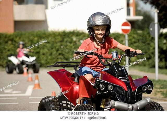 Smiling boy with quadbike on driver training area