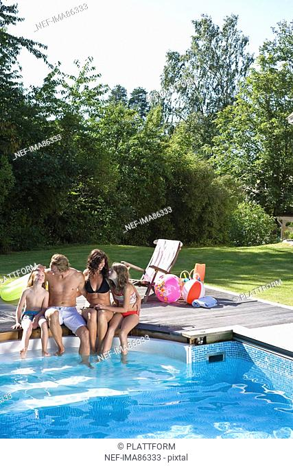 Family sitting at the edge of swimming pool