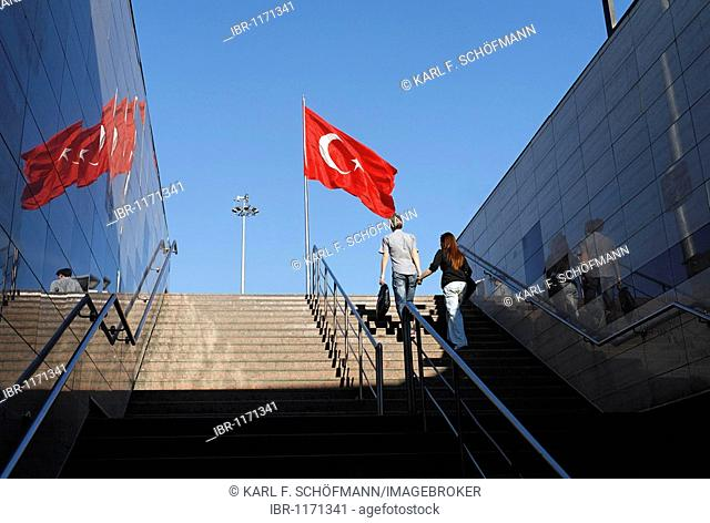 Young couple holding hands walking a flight of stairs to the top, under the Turkish flag, Taksim Square, Beyoglu, Istanbul, Turkey
