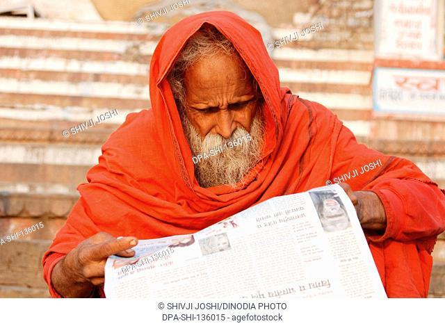 Sadhu reading newspaper at ghat of Ganga ; Varanasi ; Uttar Pradesh ; India