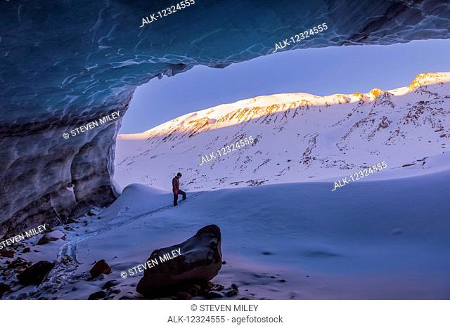 A man and the peaks of surrounding mountains at sunrise are framed by the entrance to a large ice cave within Augustana Glacier in the Alaska Range in winter