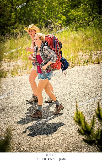 Young woman and teenage girl hiker hiking on rural road, Red Lodge, Montana, USA