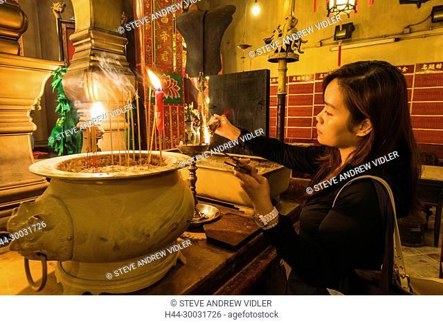 China, Hong Kong, Central, Hollywood Road, Man Mo Temple, Worshipper Lighting Incense Sticks to Taoist God Statues