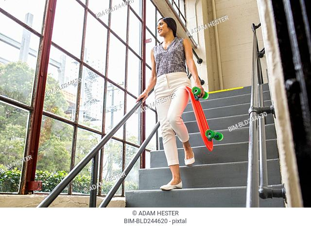 Asian woman carrying skateboard on staircase