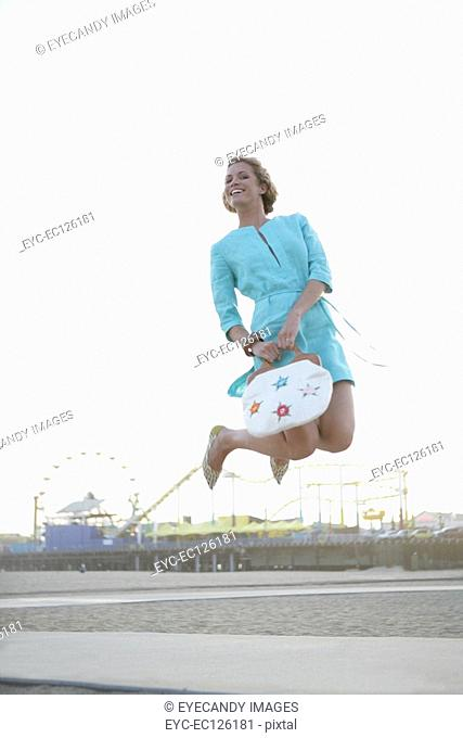 Young woman jumping in front of amusement park