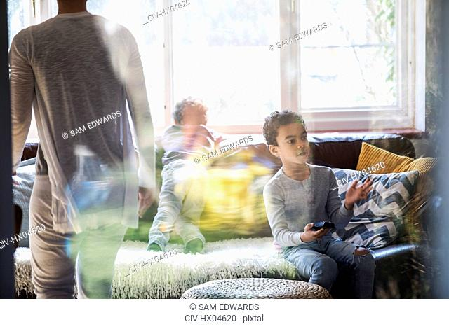Boy with remote control watching TV in living room