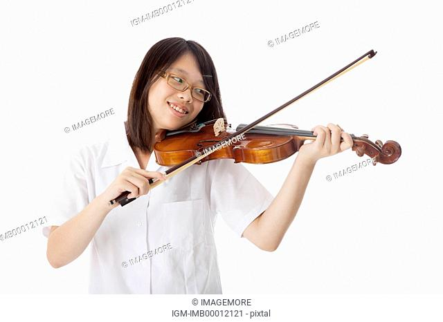 Teenage girl playing violin and looking away with smile
