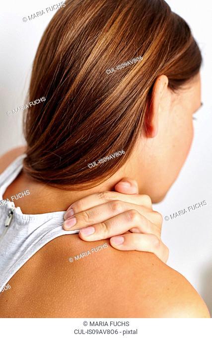 Woman massaging right shoulder