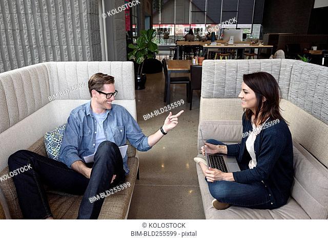 Caucasian couple sitting on sofas talking