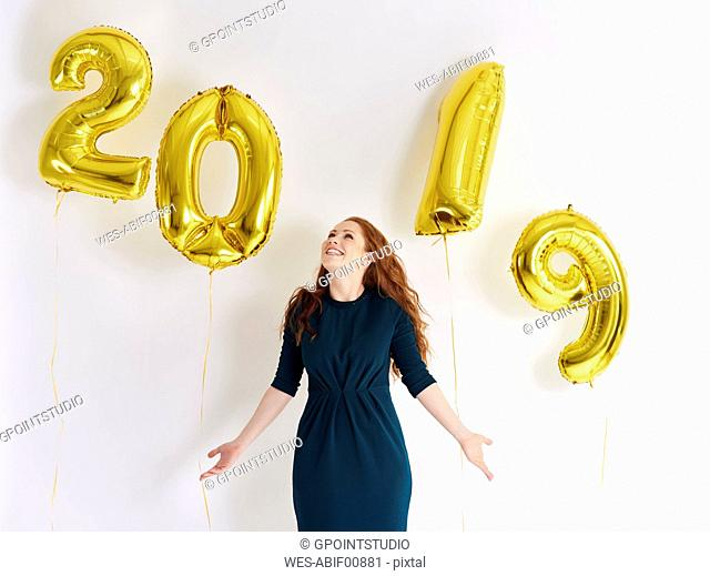 Happy young woman with golden balloons forming the date '2019'