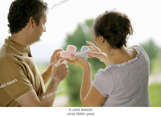 Man and woman holding up two baby boots
