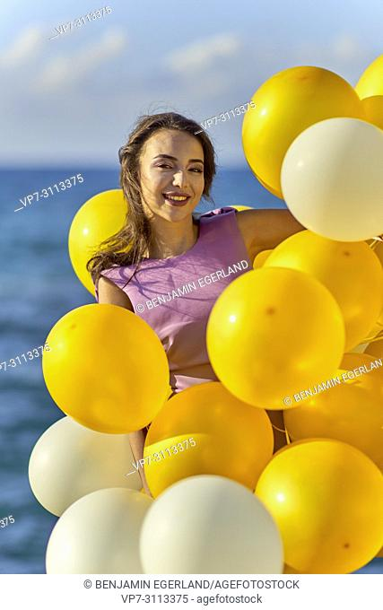 woman between balloons, at seaside