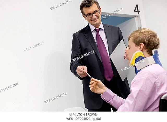 Man in suit handing over business card to patient with neck brace