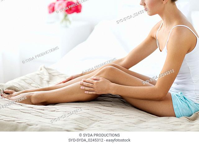 beautiful woman with bare legs on bed at home