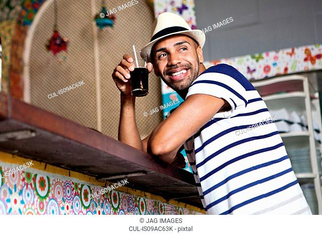 Man at counter of cafe bar, holding a drink