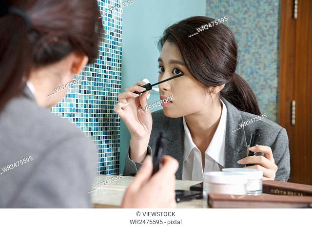 Young women is putting on makeup