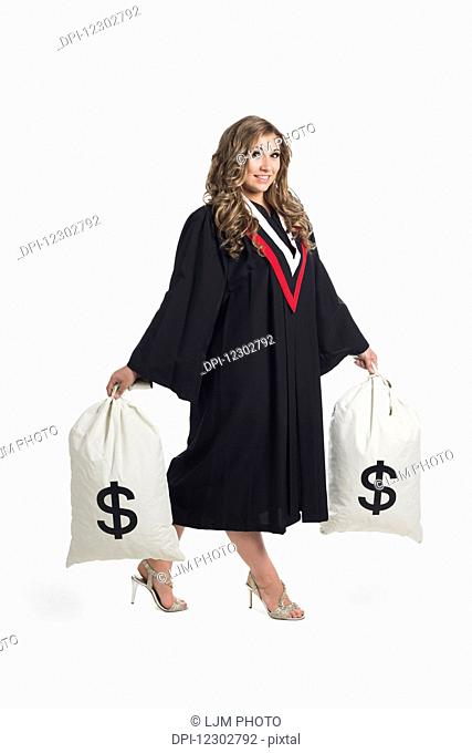 Young graduating woman holding money bags to symbolize the costs of her education; Edmonton, Alberta, Canada