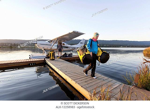 Visitor unloading gear from a flotaplane, Homer, Kenai Peninsula, Southcentral Alaska