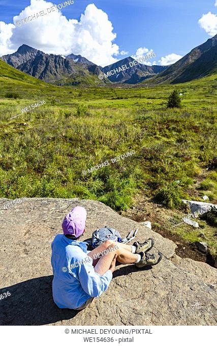 Mature woman sitting on rock along South Fork Eagle River hiking trail near Anchorage, Alaska