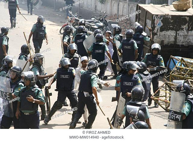 Riot police charging baton on Islamic activists during a clash on the issue of 'Women policy', in front of Baitul Mukarram mosque, in Dhaka