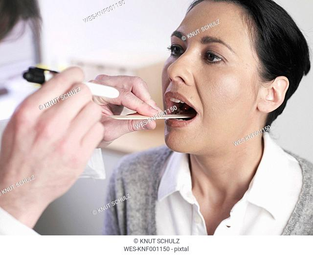 Germany, Hamburg, Doctor examining patient mouth in clinic