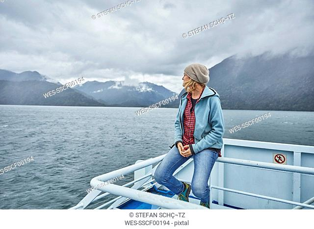 Chile, Hornopiren, woman sitting on rail of a ferry looking at fjord