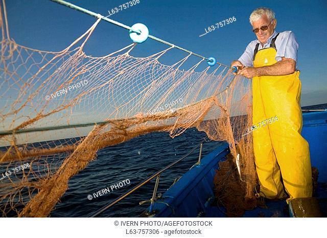 Senior fisherman fishing with nets in his boat, Cambrils. Tarragona province, Catalonia, Spain