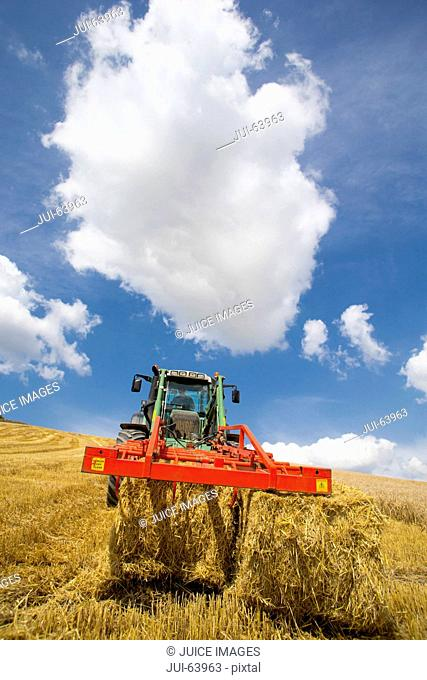 Tractor arranging straw bales in sunny rural field