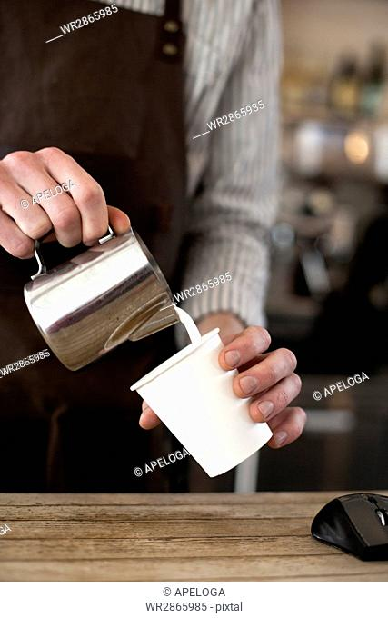Midsection of barista preparing cappuccino in coffee shop