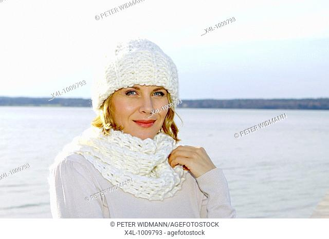 blonde woman in the late fall at a lake