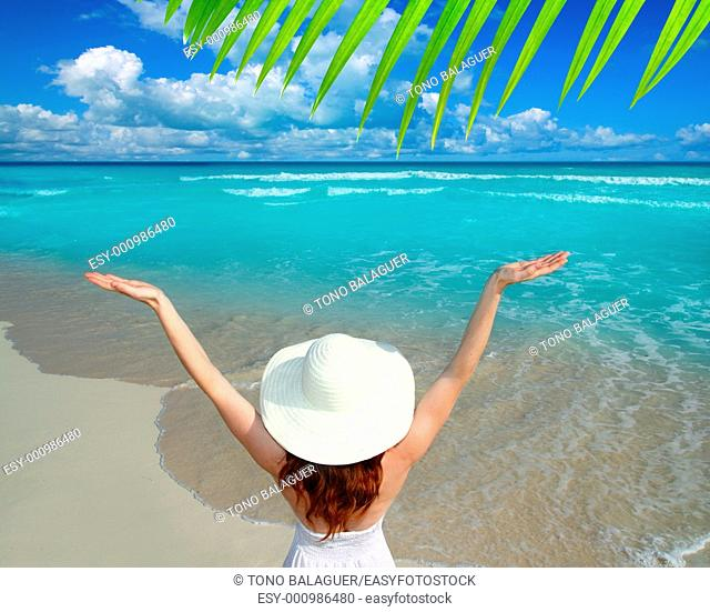 Caribbean beach woman rear view hat open arms happy vacation gesture
