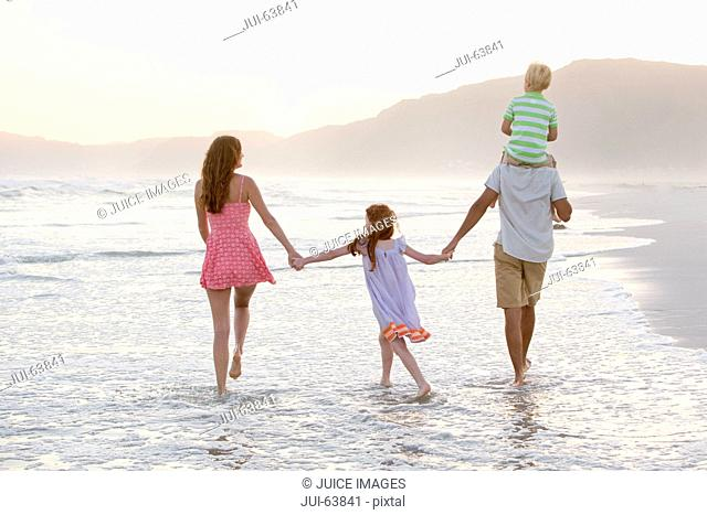 Happy family walking through waves, holding hands and son having piggy-back, on sunny beach