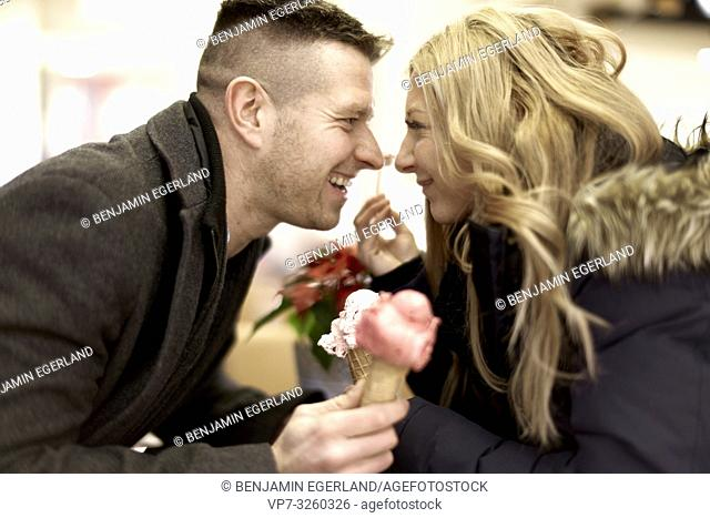 couple eating ice cream, looking at each other, in Cottbus, Brandenburg, Germany