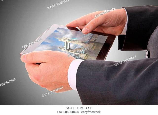 male hand holding a tablet with a photograph of London