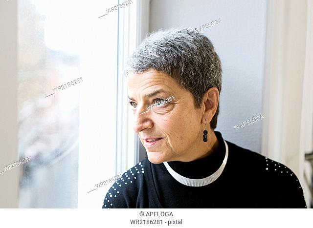 Mature businesswoman looking through window in office
