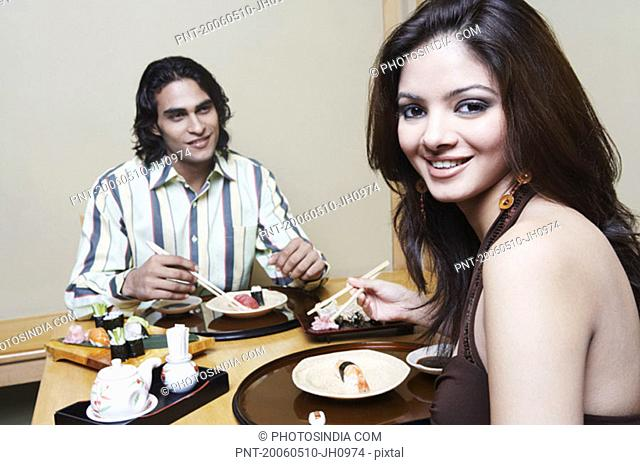 Portrait of a young woman sitting with a young man at the dining table and smiling