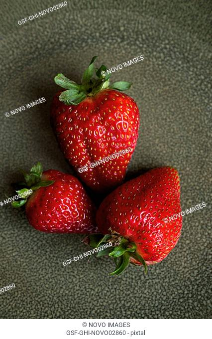Close-Up of Three Strawberries on Green Plate, High Angle View