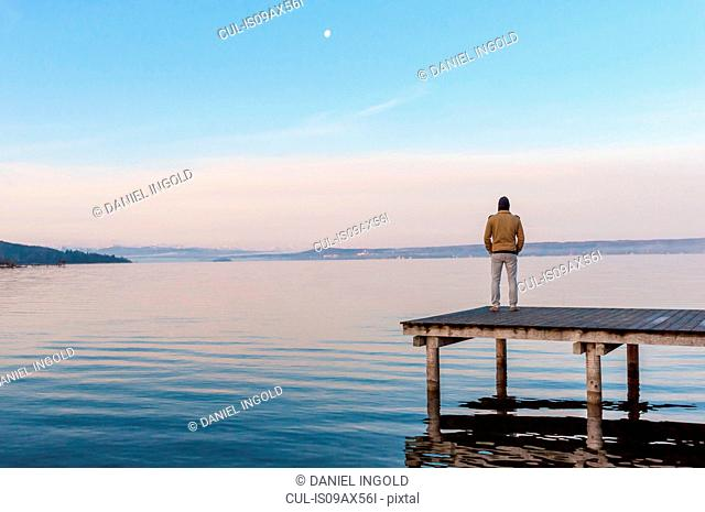 Full length rear view of man standing on wooden pier looking away at ocean