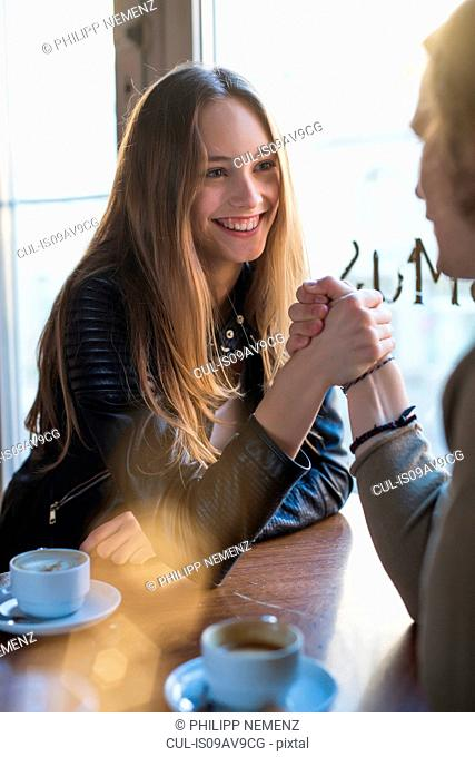 Smiling woman and young man holding hands over cafe table