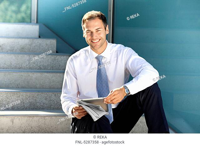 Smiling businessman sitting with tablet PC and newspaper on stairs