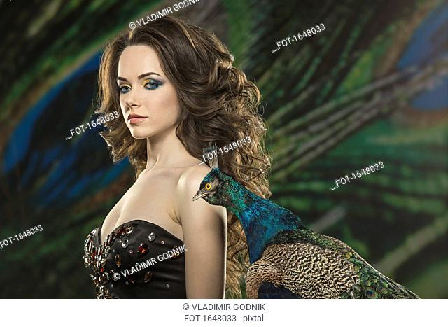 Portrait of beautiful young woman by peacock against feathers