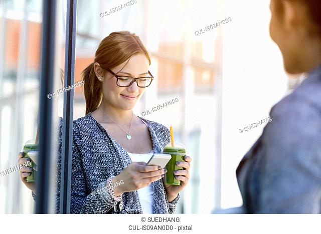 Young woman with takeaway coffee reading smartphone messages