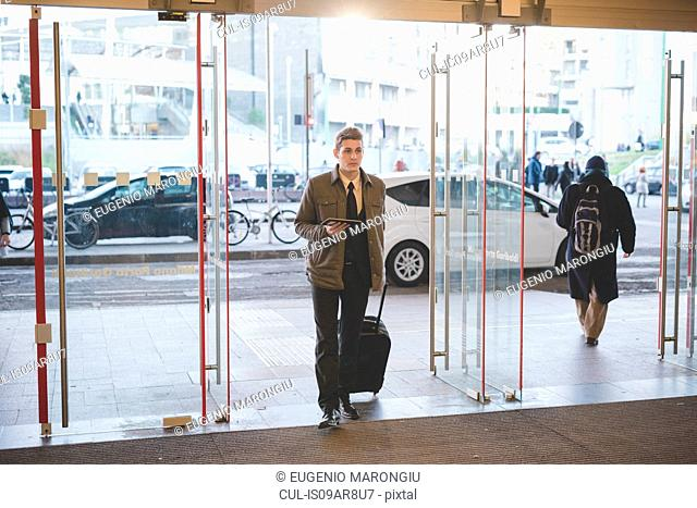 Young businessman commuter walking through glass doors with suitcase