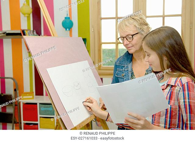 Smiling young teen girl drawing with her teacher