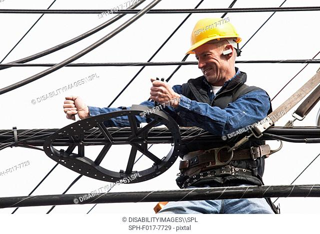Communications worker using a wrench on cable support attachments