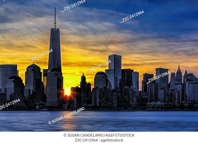 New York City Skyline At Dawn - The sun rises behind the lower Manhattan, New York City (NYC) skyline. Along One World Trade Center